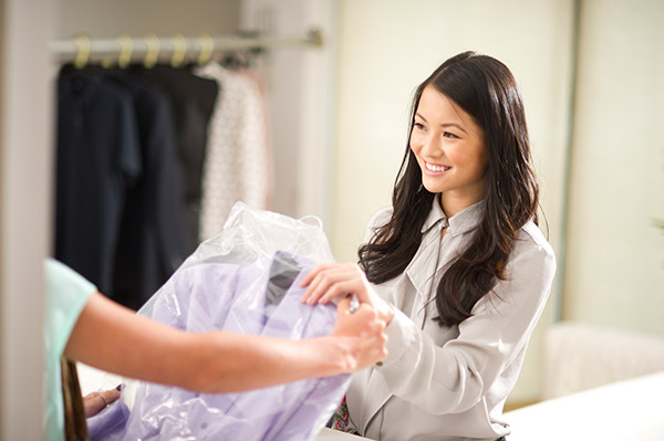 A woman receiving her dry cleaning.