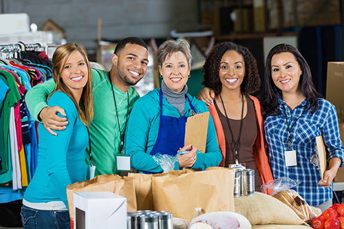 A group of happy workers posing for a photo at the local food bank